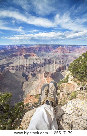 Legs Of A Resting Person On The Edge Of The Grand Canyon.