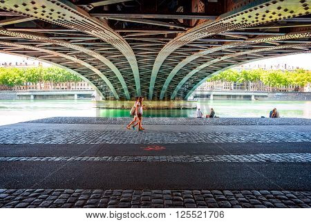 Two Women Passing Under The Bridge Near River
