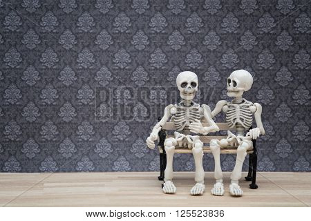two skeletons sitting on a bench chating