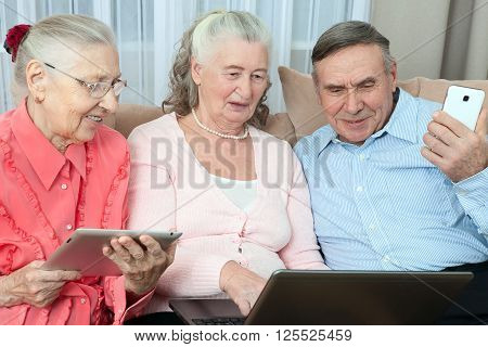 Group of older people holding a laptop, smartphone, tablet and make purchases over the Internet in the cozy living room of the house. Elderly people communicate fun close up.