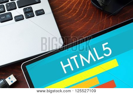 Tablet with word Html5  on a wooden background.