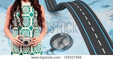 Mid section of woman holding camera against world map with compass showing north america