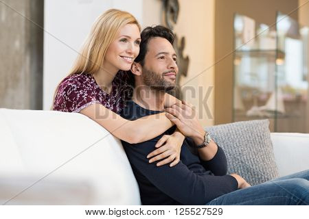 Thoughtful young couple smiling while relaxing on couch in living room. Happy couple thinking about their future and looking away. Happy couple embracing each other. Lovely couple looking forward.