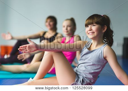 Girls and Instructor or mother doing gymnastic exercises  in fitness class.