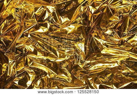 Close up wrinkled golden luminosity foil background