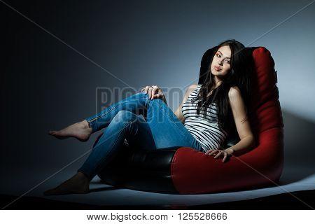 beautiful young brunette girl lying on bean bag