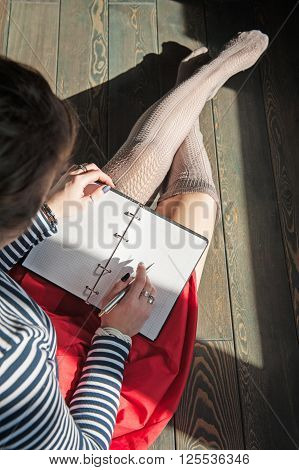 Cozy Photo Of Woman Writing In Notebook Sitting On Floor In Sunlight