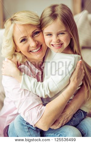 Portrait of happy beautiful granny and her granddaughter hugging looking at camera and smiling poster