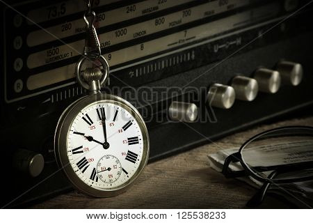 Pocket watch with radio glasses and newspaper on wooden table