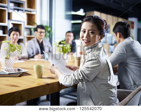 young asian designer business woman looking at camera smiling during meeting.