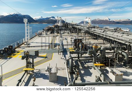 Forward part of tanker with mountains in a fiord of Norway .