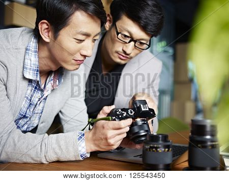 two young asian photographers designers checking pictures in camera in studio.