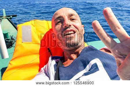 Man taking selfie on solo ocean crossing with tropical islands background - Tired male survivor to extreme travel experience - Concept of hard sea travel or clandestine migrant Mediterranean sea trip
