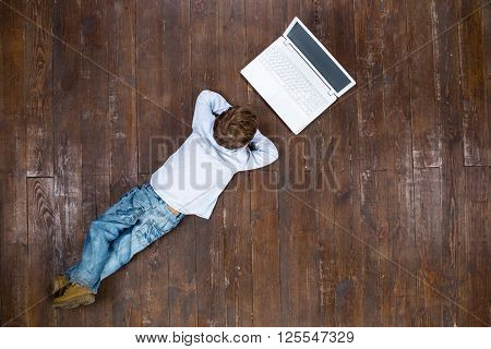Happy child. Top view creative photo of little boy on vintage brown wooden floor. Boy using laptop