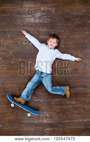 Happy child. Top view creative photo of little boy on vintage brown wooden floor. Boy riding on skateboard