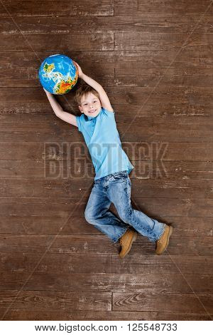 Happy child. Top view creative photo of little boy on vintage brown wooden floor. Boy holding globe, looking at camera and smiling
