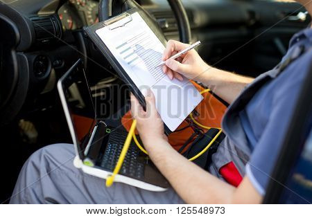 Mechanic writing on clipboard sitting in the car close up