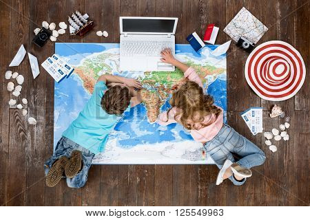 Happy children. Top view creative photo of little boy and girl on vintage brown wooden floor. Children lying on world map near travel things and using laptop