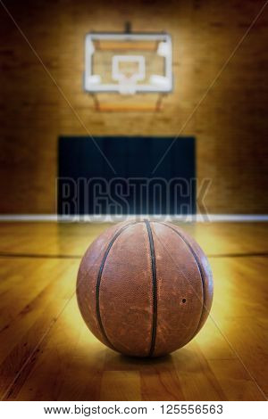 Basketball on floor of empty basketball court