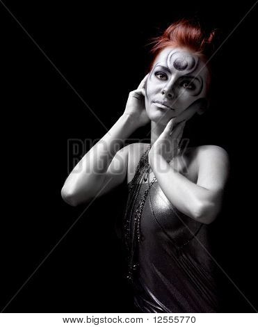 Portrait of beautiful woman with silver bodyart on black background
