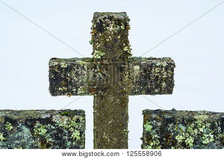 Old moss and lichen covered stonecross in cemetery