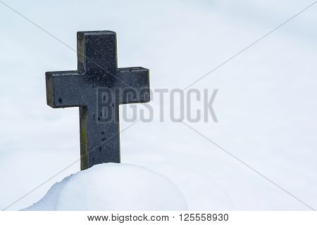 Black stonecross in cemetery in winter season