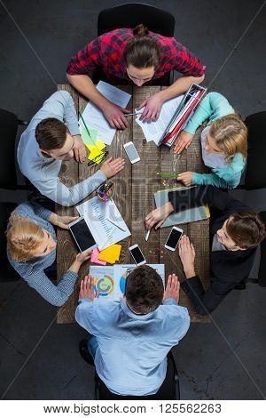 Top view creative photo of business people sitting at dark wooden vintage table. Business people having meeting. Concept for successful teamwork. There are electronic gadgets and graphics at table