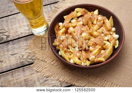 Poutine traditional Canadian meal with fries, curd cheese, beer and gravy on vintage wooden table background