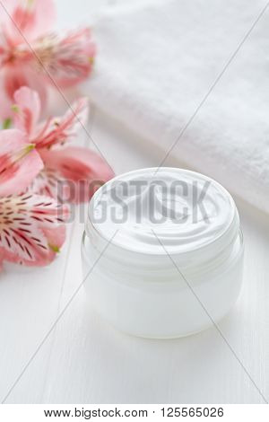 Anti wrinkle anti-aging cosmetic cream face care hygiene moisture lotion with herbal flowers therapy in glass jar with towel on white background