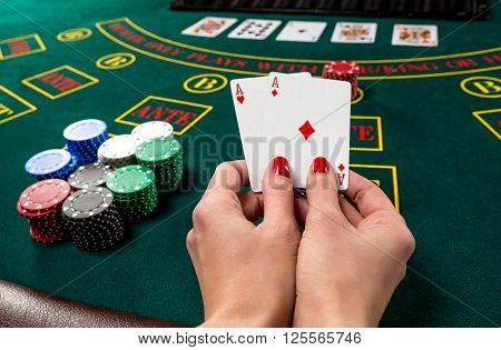 poker player holds cards. first-person view. two aces, a winning combination. female hands poster