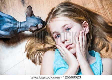 Beautiful girl with gray sphinx cat lying on flour in room portrait