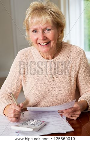 Smiling Senior Woman Reviewing Domestic Finances At Home