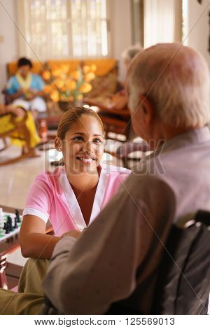 Old people in geriatric hospice: young attractive hispanic woman working as nurse takes care of a senior man on wheelchair. She talks with him then goes away to help other patients poster