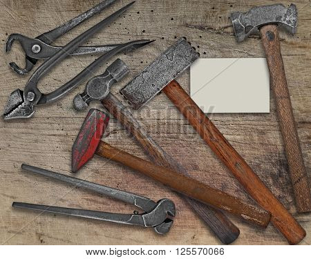 vintage blacksmith or metalwork tools over wooden bench business card for your text