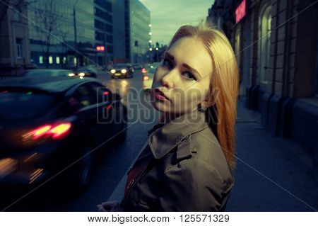 Pretty woman posing in pensive state of mind in the night street with blurred cars and streetlights on background, toned image.