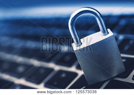 Data Security Encryption Photo Concept with Metallic Padlock on Laptop Computer Keyboard.