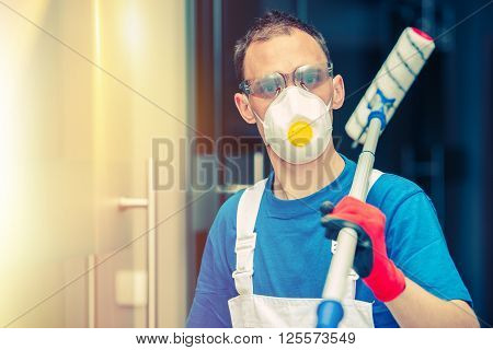 Pro House Painting. Professional House Painter with Painting Roller Safety Mask and Glasses. Indoor Painting.