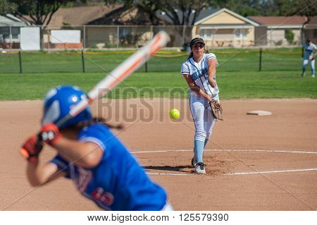 Close up of softball pitcher throwing the curve ball to the batter.