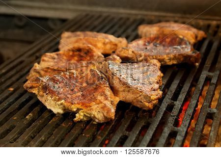 many pieces of steak broiled on a barbecue