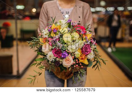 bouquet of beautiful different mixed summer flowers in woman hands
