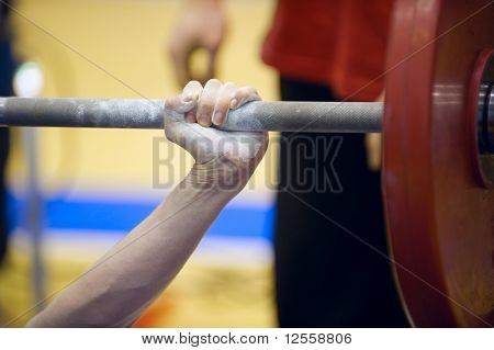 Hand lifts a iron barbell