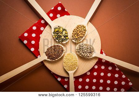 Seeds on wooden spoons which are lying at the round cutting board and red napkin - sesame, linseed, pumpkin and sunflower seeds, green lentils