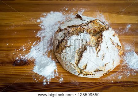 Round bread on the wooden table with flour around