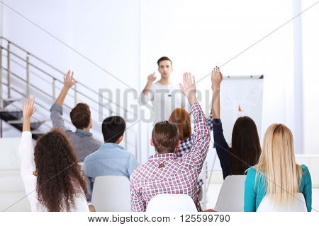 Young colleagues raising hands at the business meeting in office