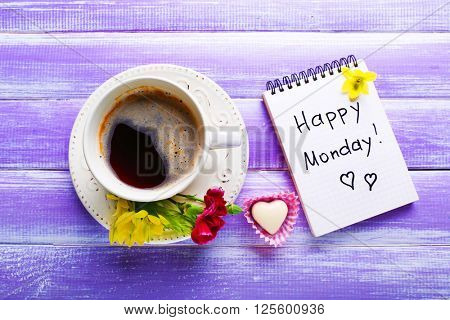 Cup of coffee, chocolate candy, flowers and note HAPPY MONDAY on wooden background