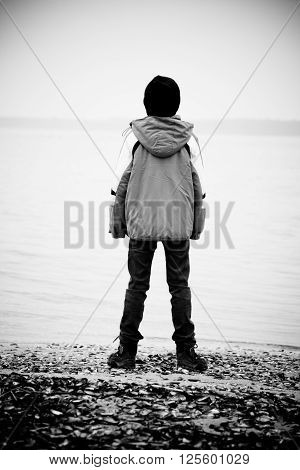 Rear View On Boy Facing Lake