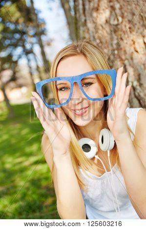 Young blonde woman with hipster nerd glasses in summer in a park
