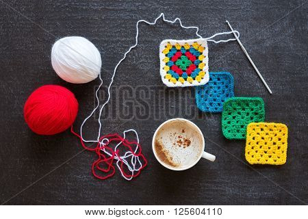 Balls of red and white yarn, crocheted motifs and a cup of coffee on grunge black background.