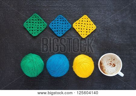 Balls of green, blue, yellow yarn, crocheted motifs and a cup of coffee on grunge black background.