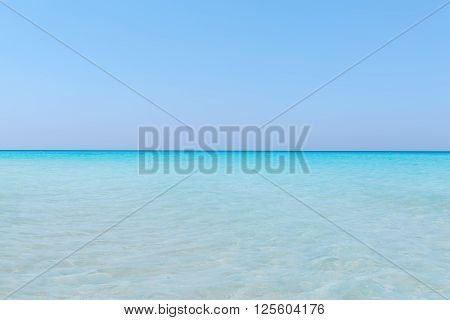 Amazing gorgeous natural background of turquoise tranquil ocean merging with clear beautiful sky at horizon line on sunny warm day